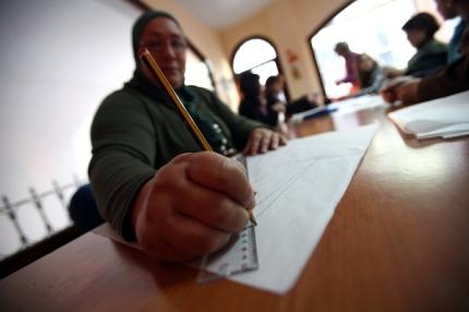 Una inmigrante rellenando unos papeles