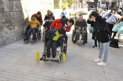 Varios escolares en sillas de ruedas sortean algunos obstáculos en un circuito urbano.