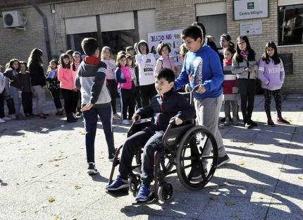 Paseo en silla de ruedas por el patio del colegio, uno de los talleres.