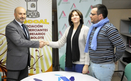 Joaquín García, gerente de Nexolan, y Ana JIménez, presidenta de ASCOAL, se estrechan la mano en presencia de Pedro Moreno, secretario de ASCOAL, tras la firma del acuerdo.