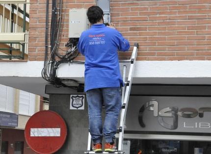 Un técnico de Radiokable manipula uno de lo cajetines de fibra instalado en Albolote