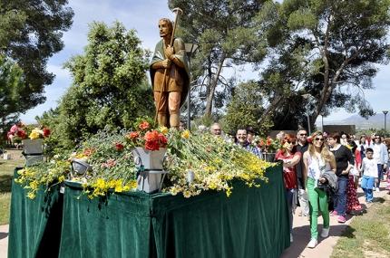 Entrada de la carroza de San Isidro en el paraje de Los Pinos acompañada por numerosos romeros y romeras.