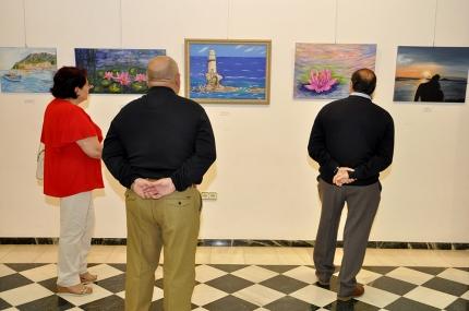 Varios visitantes echan un vistazo a las obras expuestas el día de la inauguración de la muestra.