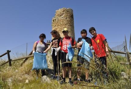Alumnado de secundaria con sus bolsas recogiendo basura en la base del Torreón de Albolote
