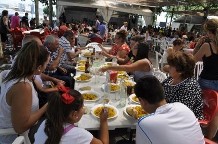Vecinos y vecinas degustando un plato de la paella popular