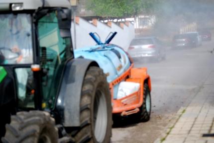 Un tractor nebuliza líquido desinfectante en una de las calles de la urbanización Monte Elvira esta mañana.