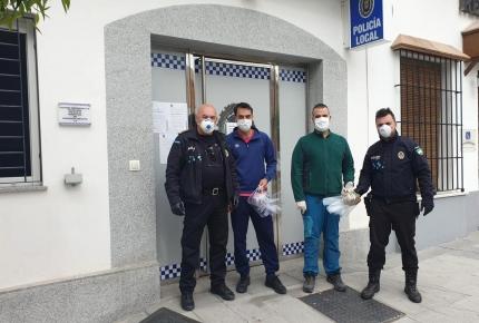 Los dos jóvenes, centro, junto a represetantes de Policía Local en el momento de la entrega de las máscaras.
