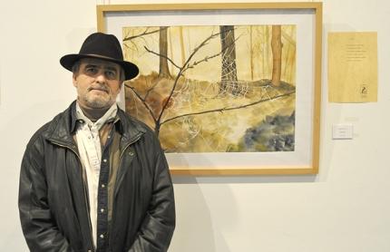 El escritor y poeta, Emilio Ballesteros, frente al cuadro `Ananse` de la pintora malagueña, Ángela García.